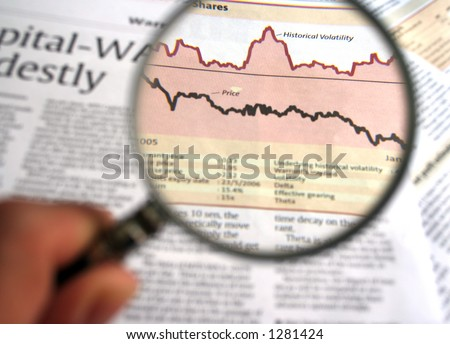 Hand holding a magnifying glass focusing on a chart in the business section of the newspaper. - stock photo