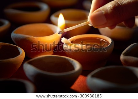 Hand holding a matchstick lighting diya lamps during diwali celebration  - stock photo