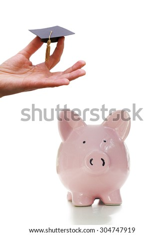 Hand holding a miniature graduation cap, with piggy bank, on white