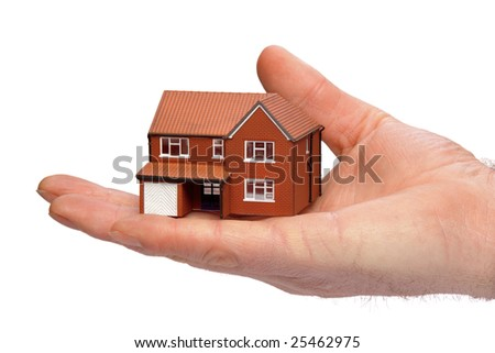 Hand holding a miniature modern detached house isolated on a white background