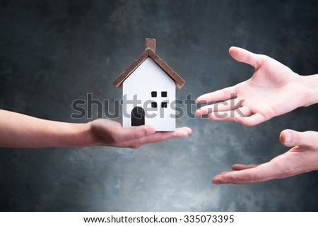 Hand holding a model of house - stock photo
