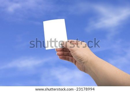 Hand holding a neutral ticket against a blue sky - isolated