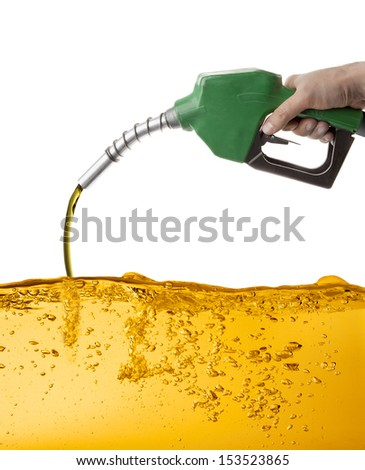 Hand holding a nozzle pumping gasoline in a tank - stock photo