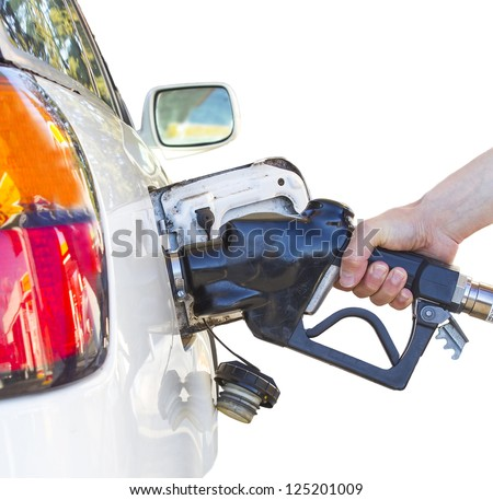 Hand holding a nozzle while fueling white car.  Focus on the nozzle. - stock photo