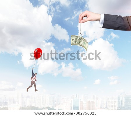 hand holding a one-hundred dollar banknote on a thread, a young businessman flying on a red balloon to it. City and blue sky at the background. Concept of motivation. - stock photo