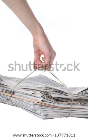Hand holding a pack of newspaper for recycling - stock photo