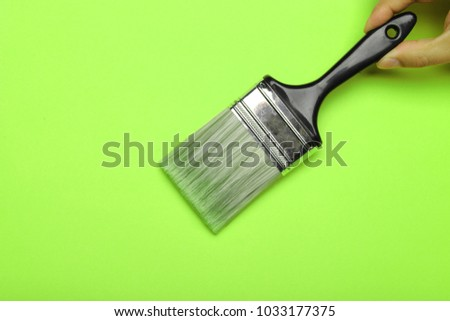 Hand holding a paint brush isolated on a bright green background