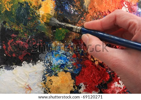 Hand holding a paintbrush on an abstract oil painting. Focus on brush and painting, not on the hand. - stock photo
