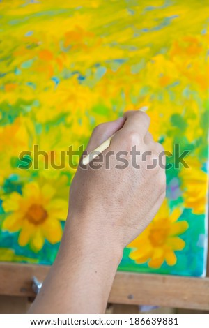 Hand holding a paintbrush on flower oil painting - stock photo
