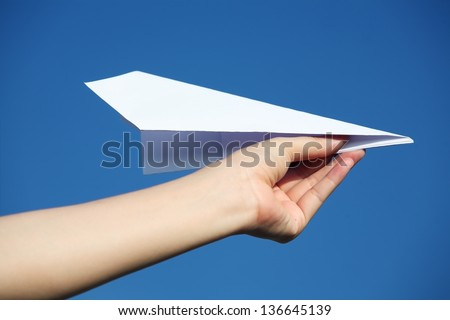hand holding a paper airplane against a blue sky - stock photo