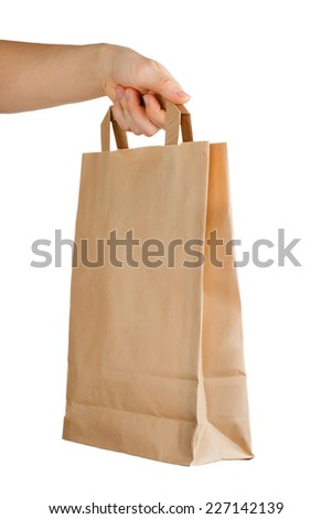 Hand holding a paper bag isolated on white background. Delivery concept - stock photo