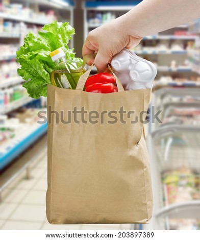 hand holding a paper bag with groceries in a supermarket - stock photo