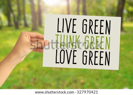 Hand holding a paper card with Live green, Think green, Love green word on abstract nature background - stock photo