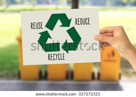 Hand holding a paper card with the recycling sign