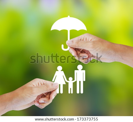 Hand holding a paper family and umbrella on green background - stock photo