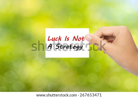 Hand holding a paper Luck Is Not A Strategy on green background  - stock photo