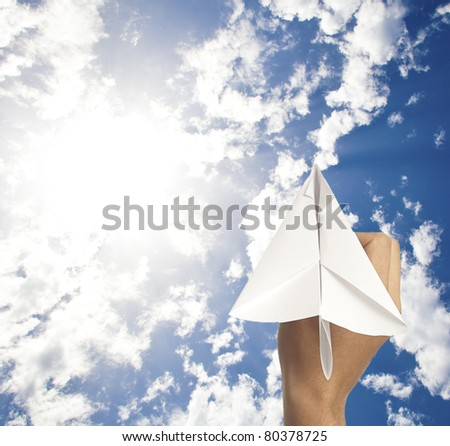 hand holding a paper plane on a white background - stock photo