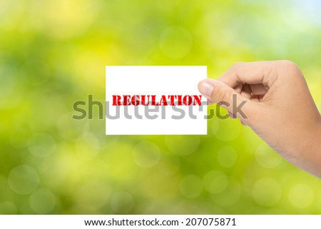 Hand holding a paper REGULATION on green background - stock photo