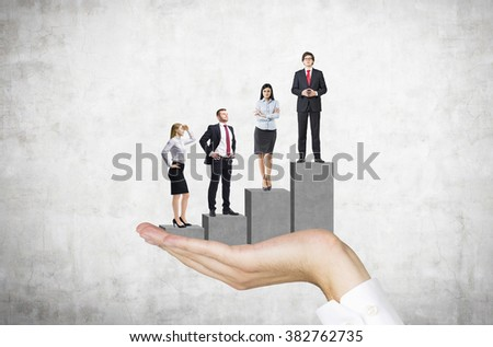 hand holding a pedestal in the shape of a bar chart, four businesspeople standing on it. Front view. Concrete background. Concept of career growth. - stock photo
