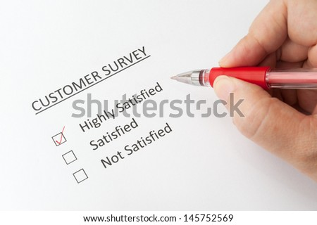 Hand holding a pen and filling a  customer survey with options of highly satisfied, satisfied and not satisfied