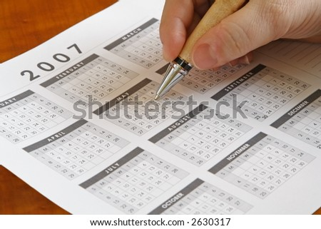 Hand holding a pen on a calendar - stock photo