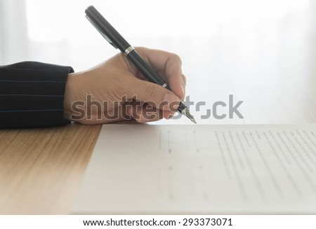 hand holding a pen to sign approval  about to sign a letter - stock photo