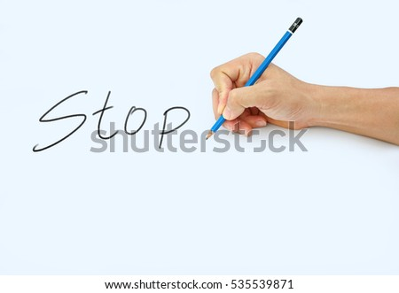 "Hand holding a pencil on a white paper background, writing with pencil for word "" Stop """