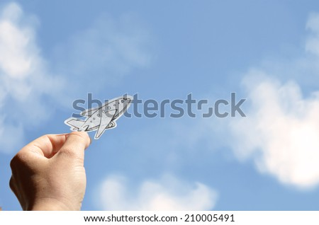 Hand holding a picture of plane on a sky background - stock photo