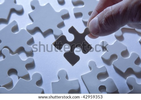 Hand holding a piece of a jigsaw puzzle, silhouetted against a background of more puzzle pieces