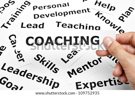 Hand holding a piece of paper with Coaching written on it. - stock photo