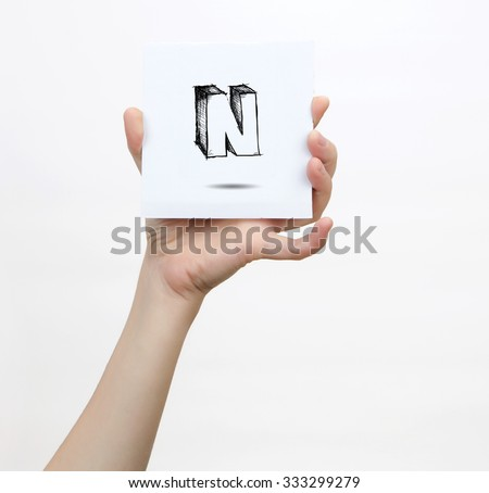 Hand holding a piece of paper with sketchy capital letter  N, isolated on white.