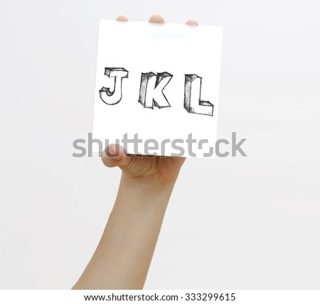 Hand holding a piece of paper with sketchy capital letter s J K L, isolated on white. - stock photo