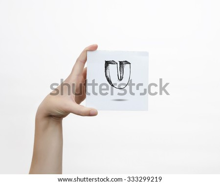 Hand holding a piece of paper with sketchy capital letter  U, isolated on white. - stock photo