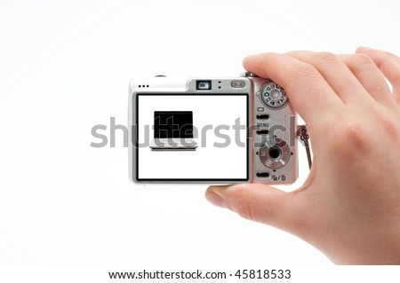 Hand holding a point and shoot camera and photographing a laptop