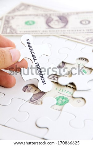 hand holding a puzzle piece, financial freedom concept  - stock photo