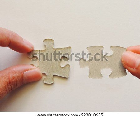 hand holding a puzzle piece on white background,Concept collaboration in business.
