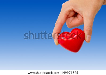 Hand holding a red heart - stock photo