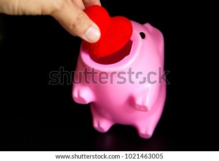 Hand holding a red heart to put in a pink piggy bank on black background. Ideas for Valentine's Day