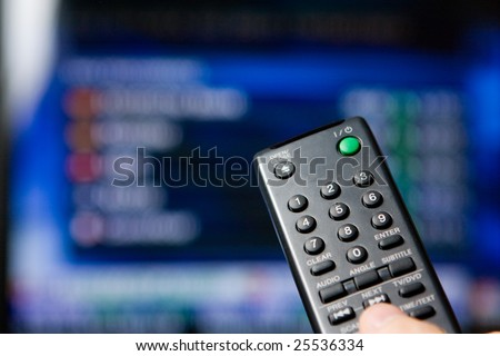Hand holding a remote control pointing to a blurred TV program - stock photo