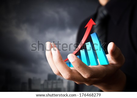 Hand holding a rising arrow, representing business growth. - stock photo