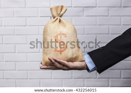 Hand holding a sack of money and white brick background - stock photo