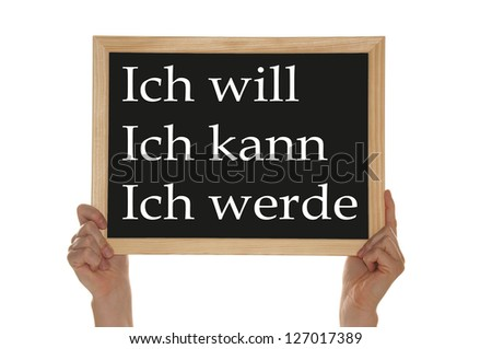 Hand holding a sign with the german words I can, I will, I will / Sign Concept