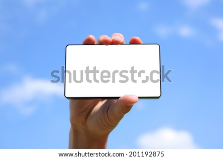 hand holding a smart phone device on a blue sky background - stock photo