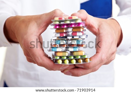 Hand holding a stack of many different pills - stock photo