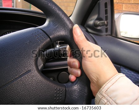 hand holding a steering wheel when driving - stock photo