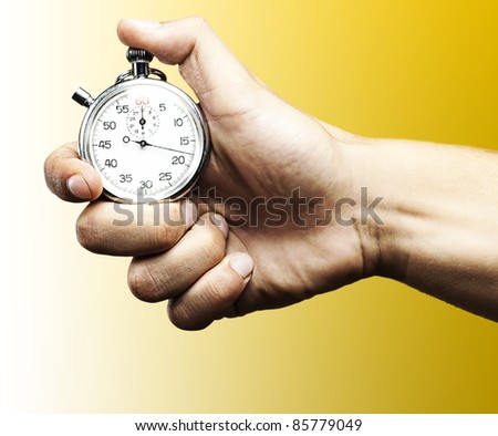 hand holding a stopwatch against a blue background - stock photo