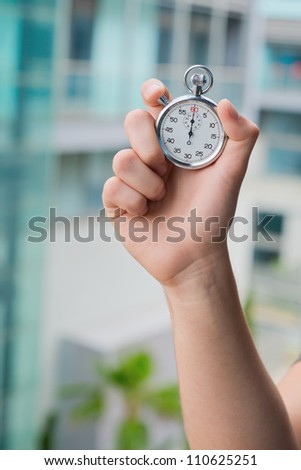 Hand Holding A Stopwatch, Outdoor - stock photo