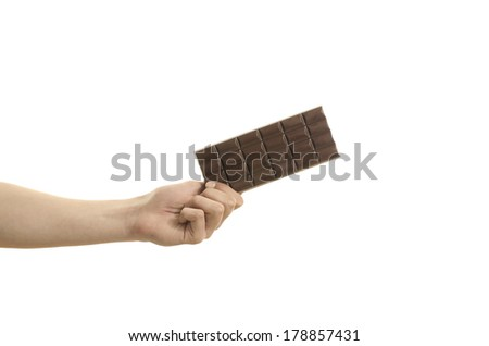 Hand holding a tablet of chocolate, isolated on white - stock photo