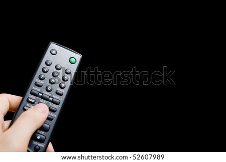 Hand holding a tv remote control against black background with copy space - stock photo