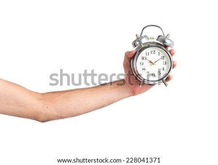 Hand holding a vintage clock over white background - stock photo